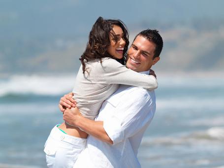 Фото Счастливая пара в белом обнимается на берегу моря