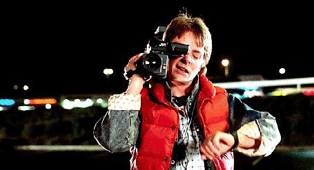 Фото Мужчина снимает на камеру, пытаясь при этом посмотреть на часы, Michael J. Fox / Майкл Дж.Фокс, кадр из фильма Back to the future / Назад в будущее