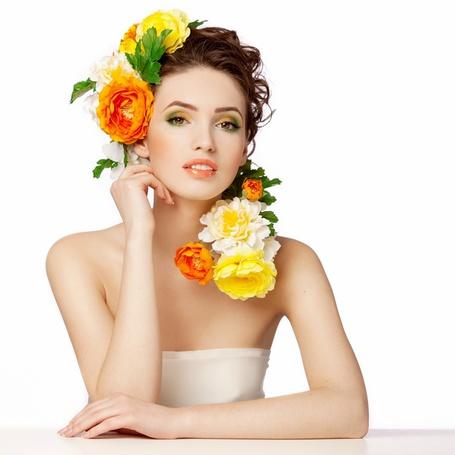 Фото Девушка в белом платье подняла руку к голове, ее волосы украшены косой с цветами роз разного цвета и зеленых листьев