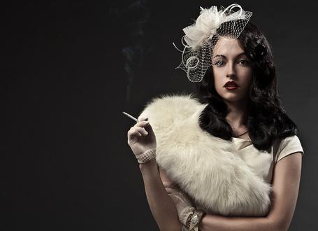 Фото Девушка стоит в белой шляпке с вуалью и цветком, в белом платье и меховой накидке на плече, с сигаретой в руке