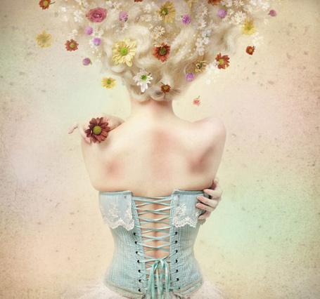 Фото Девушка-блондинка в корсете, с цветами в волосах, повернулась спиной и держит в одной руке цветок