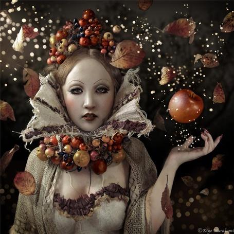 Фото Девушка-осень с овощами на голове и с ожерельем из овощей на шее подбросила рукой вверх яблоко, вокруг летают желтые листья и белые шарики