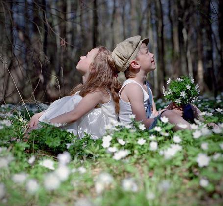 Фото Мальчик и девочка сидят спинами друг к другу на лужайке с цветами, подняв головы вверх. Мальчик держит в руках букетик цветов