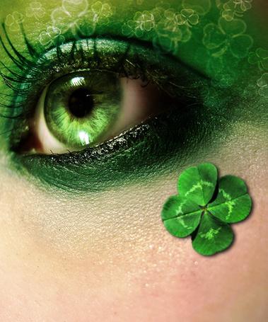Фото Зеленый глаз девушки  с макияжем под цвет листочка, который приклеен рядом