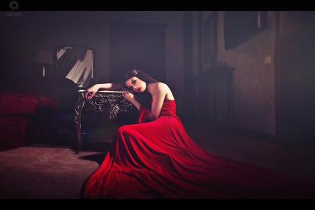 Фото Девушка в красном платье прилегла на стол