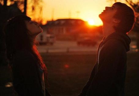 Фото Парень и девушка стоят напротив друг друга, подняв головы в верх