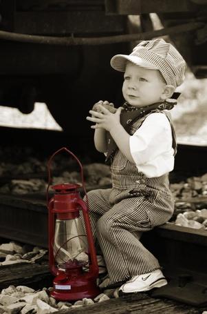 Фото Мальчик с фонарем сидит на рельсах возле колес поезда