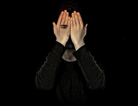 Фото Парень закрыл лицо руками и через ладонь виден глаз