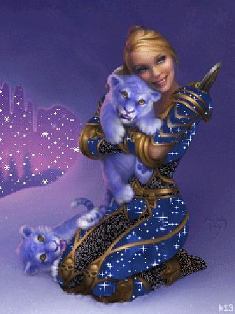Фото Девушка в блестящих доспехах с тигрятами. Один тигренок на руках, второй держится за ногу девушки