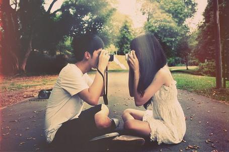 Фото Девушка и парень фотографируют друг друга сидя на асфальте
