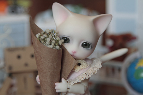 Фото Игрушечная кошка держит в лапках букет цветов