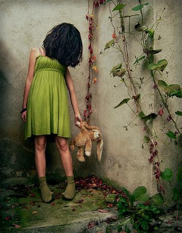 Фото Девочка в зеленом платье, стоя у стены, увитой плющом, держит за лапу игрушечного зайца