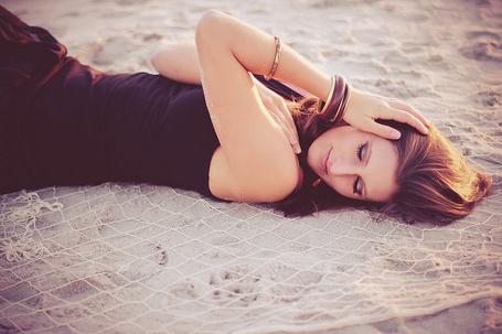 Фото Девушка с закрытыми глазами лежит на песке