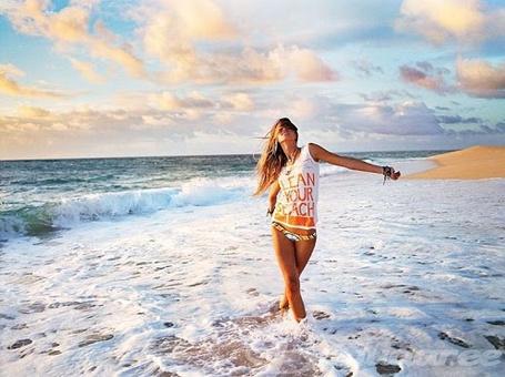 Фото Счастливая девушка идет по краю прибоя