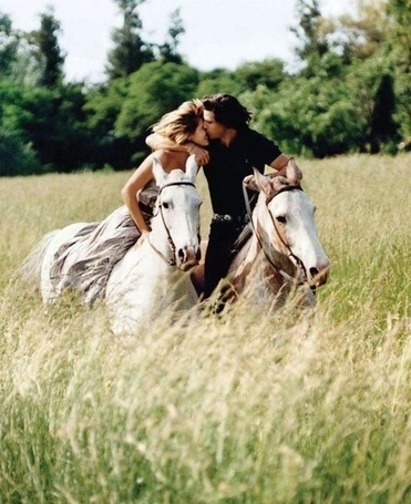 Фото Мужчина целует девушку, когда они вместе скачут на двух белых лошадях в поляне с высокой травой позади деревьев