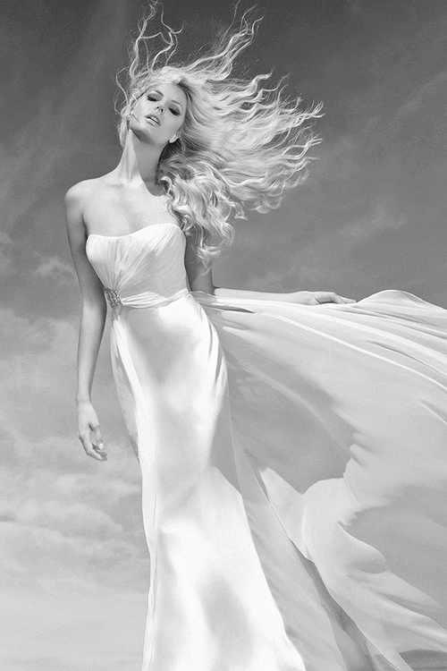 Фото Блондинка в длинном платье с развевающимися волосами