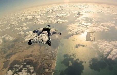 Фото Мужчина в костюме летит в небе над городом