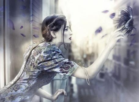 Фото Девушка на балконе прикоснулась рукой к рыбе парящей в воздухе