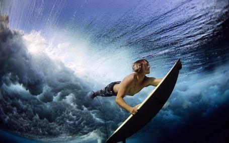 Фото Серфер Стю Джонсон / Stu Johnson, держась за свою доску, погружается под воду, фотограф Люся Григги / Lucia Griggi
