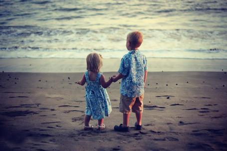 Фото Маленькая девочка в платье и маленький мальчик в рубашке из одинаковой ткани стоят на пляже, держась за руки