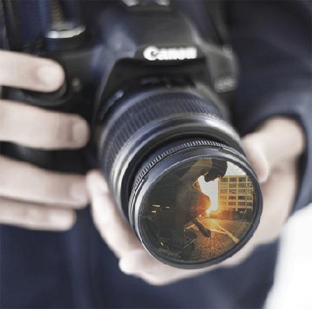 Фото Мужчина держит в руках фотоаппарат фирмы Canon, в котором видно, как другой мужчина прыгает на скейтборде