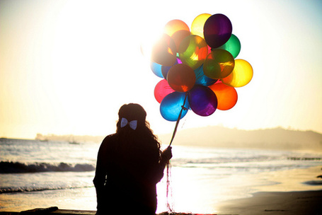 Фото Девушка с разноцветными воздушными шарами смотрит на море