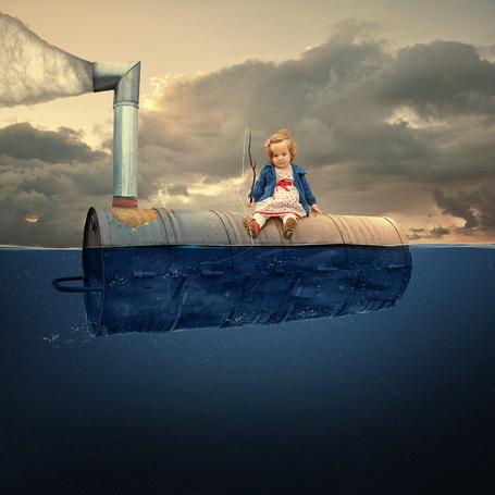 Фото Милая белокурая девочка, сидящая на металлической бочке с дымящейся трубой, плывущая по воде держит в руке прутик с привязанной ниткой и красным поплавком на фоне пасмурного неба, фотография Caras iount