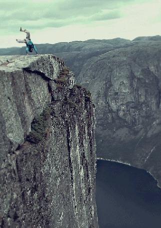 Фото Мужчина прыгает с парашютом с горы и другой снимает его на камеру