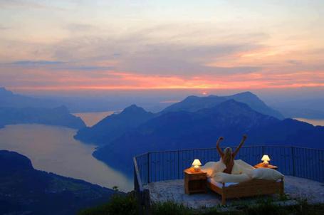 Фото Девушка проснулась на краю горы в кровате и лампочками по бокам