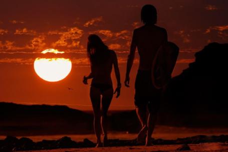 Фото Девушка и мужчина с доской для серфинга идут на фоне заката