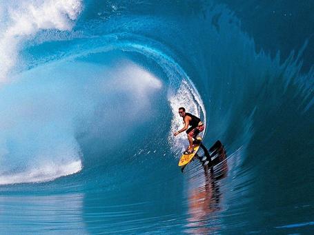 Фото Мужчина на доске для серфинга покоряет волну