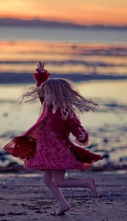 Фото Босая девочка в розовом платье подняла руку вверх танцуя у моря