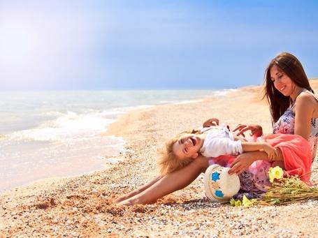 Фото Счастливая мать со смеющейся дочкой, лежащей у нее на коленях, сидят на морском берегу