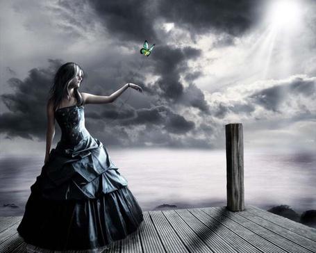 Фото Девушка стоит в темно-синем платье приподняв руку вверх, к которой привязана нить с бабочкой