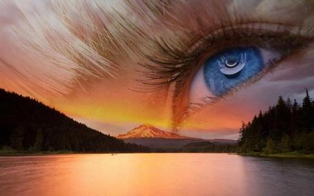 Фото Глаз девушки изображен на небе, над горами, перед разлившейся рекой, по обе стороны которой растет лес