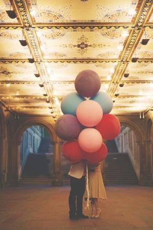 Фото Девушка с мужчиной стоят с разноцветными воздушными шарами