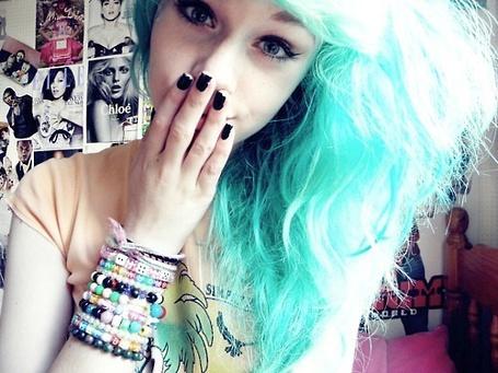Фото Девушка с волнистыми, голубыми волосами прикрывает рукой рот