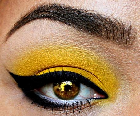 Фото Глаз девушки с отражением в нем комнаты и желтым макияжем