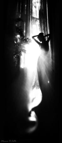 Фото Девушка, с поднятыми к голове руками, стоит в лучах дневного света у окна, фотограф Mecuro B Cotto
