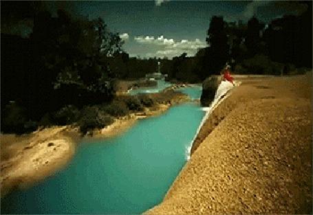 Фото Девушка в красном платье прыгает в воду, рядом пролетает попугай ара, кадр из клипа Amethyste - Moonlight Rain