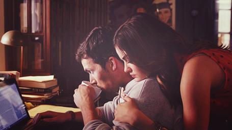 Фото Девушка обняла парня за плечи, пока тот пьет кофе и смотрит в ноутбук