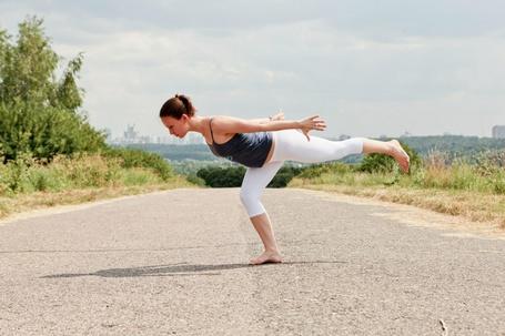 Фото Девушка исполняет асану из хатха йоги на пустынной дороге