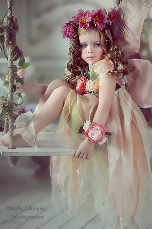 Фото Девочка с венком из цветов на голове и шикарном платьице сидит на качели, фотограф Наталья Законова