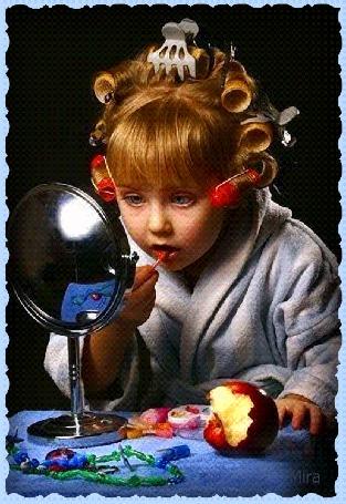 Фото Девочка с бигудями на голове подкрашивает губы стоя у зеркала