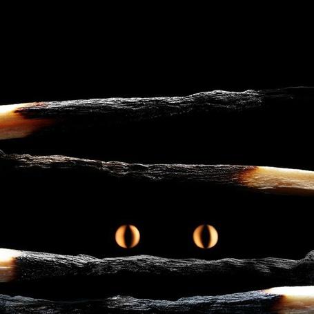Фото Огненные глаза сквозь обугленные спички на черном фоне