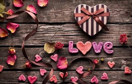 Фото Возле коробочки в виде сердца лежит надпись love / любовь, рядом разбросаны лепестки
