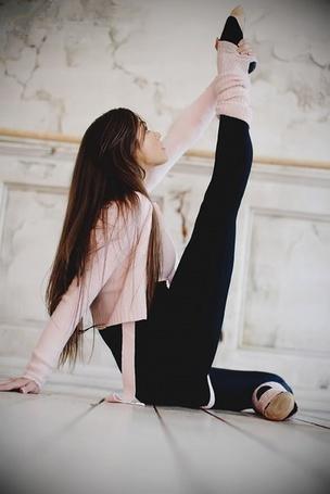 Фото Девушка с длинными темными волосами в розовой кофте растягивает мышци ног