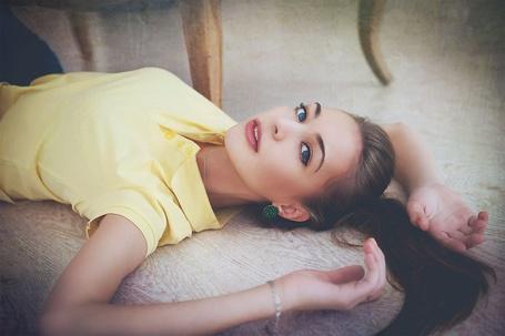 Фото Девушка в желтой майке и хвостиком на голове лежит на полу