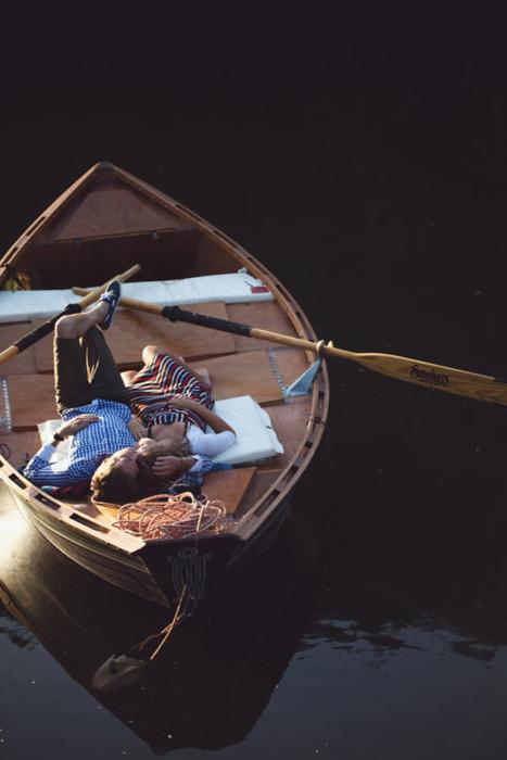 Фото Парень и девушка обнимаются, лежа на лодке посреди озера