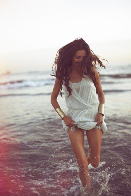 Фото Девушка в белом платье бежит по берегу моря
